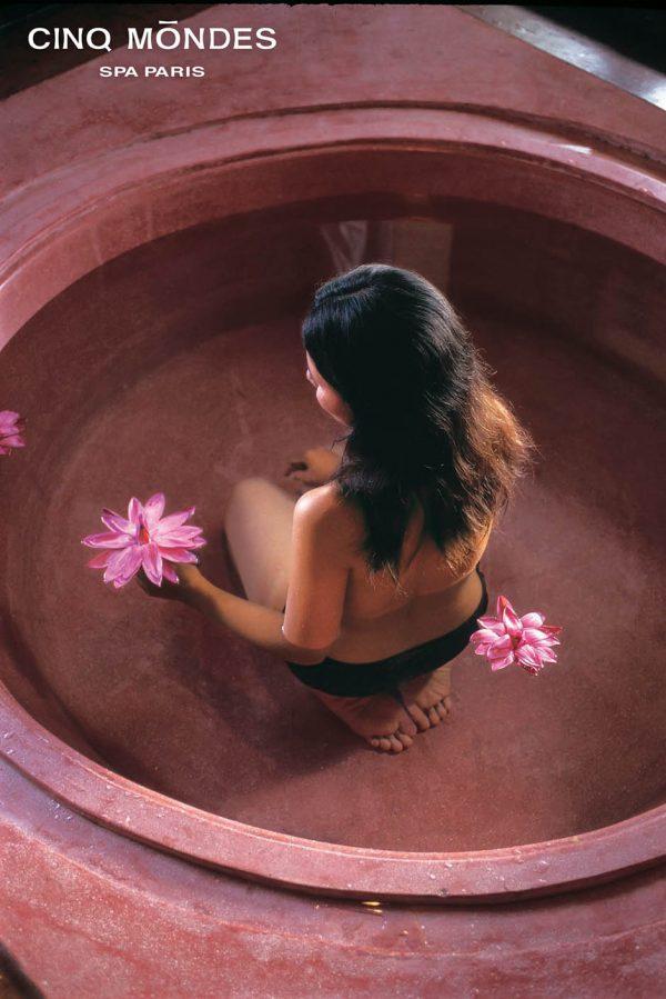 Femme de dos dans un bain avec des fleurs