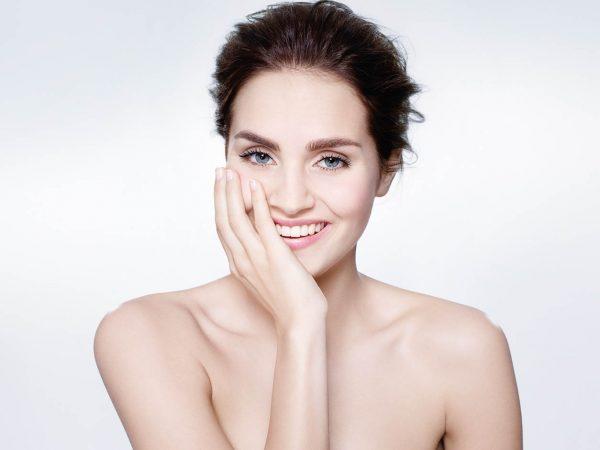 Portrait d'une femme qui sourie avec une main sur le visage