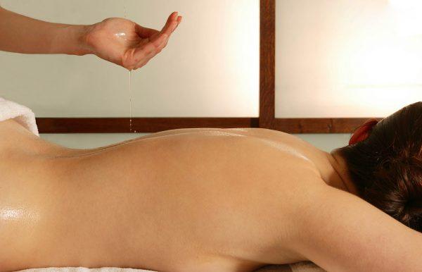 Main versant de l'huile sur le dos d'une femme pour massage